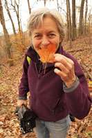 Photo of Barbara Ryersen in woods with a maple leaf.